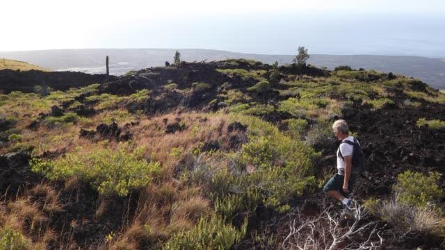vídeos y material grabado en eventos de stock de hombre camina a través de un paisaje volcánico, con mochila - un solo hombre maduro