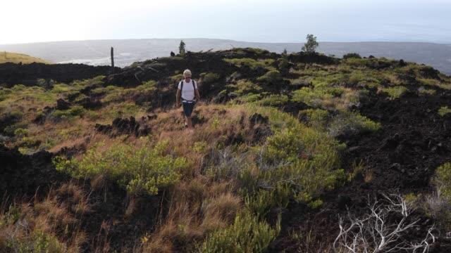stockvideo's en b-roll-footage met man loopt over vulkanische landschap, het dragen van de rugzak - alleen oudere mannen