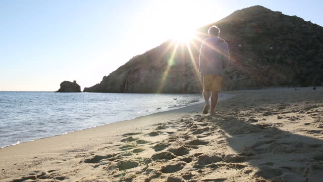 Man walks along beach at sunrise, near water's edge