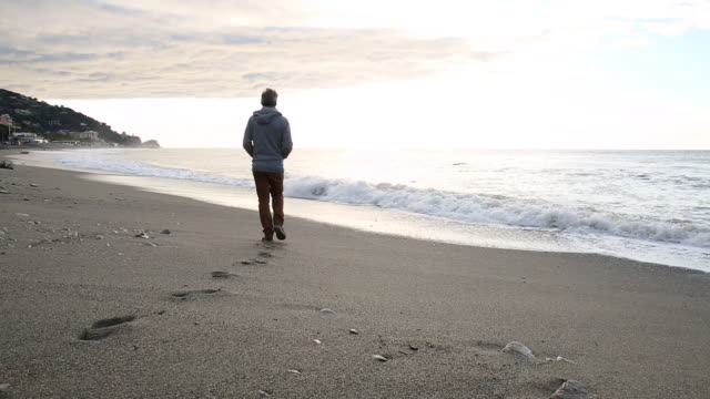 man walks along beach near surf edge, looks over sea - impronta del piede video stock e b–roll