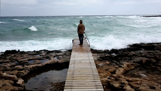 stockvideo's en b-roll-footage met man walks along boardwalk above sea, looks off - pier