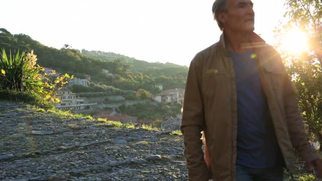 Man walks along cobblestone path, above village