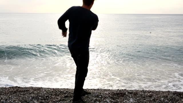 Man walks along deserted beach to sea, skips rock