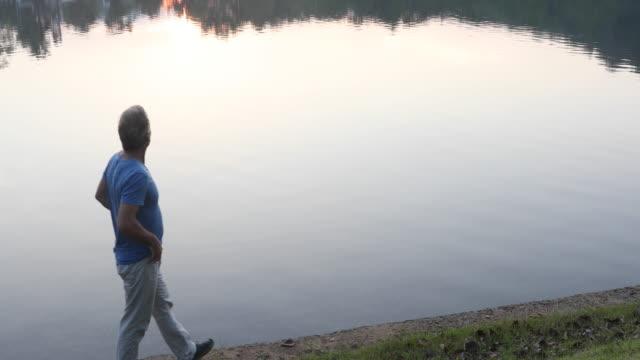 Man går längs kanten av sjön, vid soluppgången