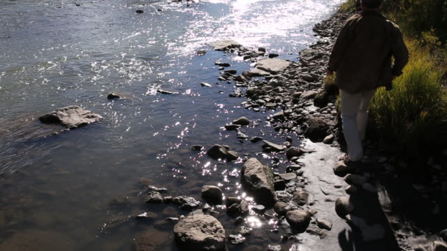 man walks along edge of mountain river, takes pic - one mid adult man only stock videos & royalty-free footage