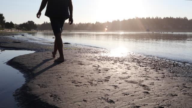 vídeos de stock e filmes b-roll de man walks along empty beach at sunrise - só homens maduros