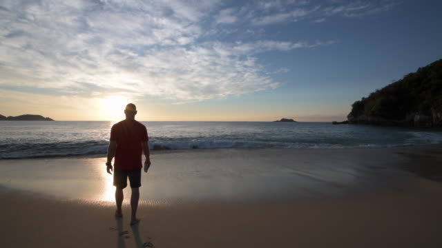 man walks along empty beach - solitude stock videos and b-roll footage