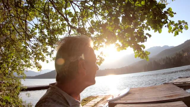 man walks along lake pier at sunrise - pier stock videos & royalty-free footage