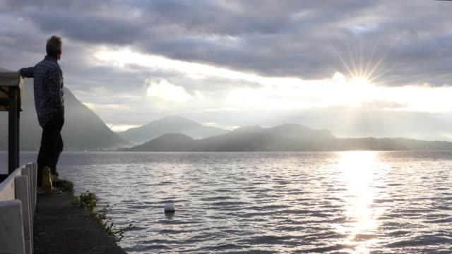 man walks along ledge and looks out across lake at sunrise - solitario video stock e b–roll