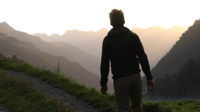 Man walks along mountain track at sunrise, looks off