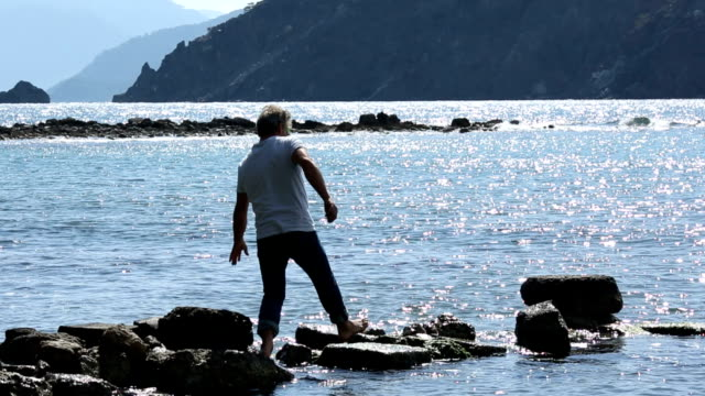 man walks along rocky pier into sea shallows, looks off - mediterranean turkey stock videos and b-roll footage