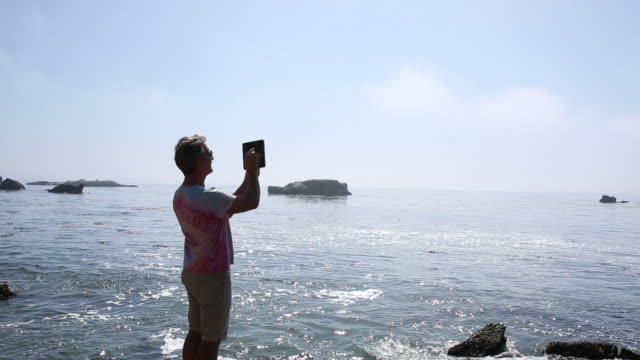 Man walks along rugged shoreline and takes photo with digital tablet
