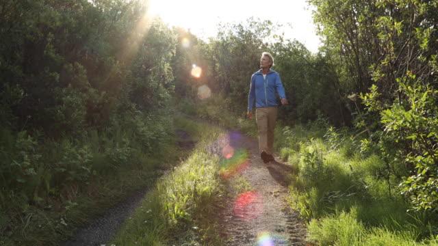 Man walks along rural track at sunrise