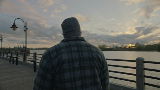 man walks along scenic riverwalk by the cape fear river in downtown wilmington, north carolina. - wilmington north carolina stock-videos und b-roll-filmmaterial