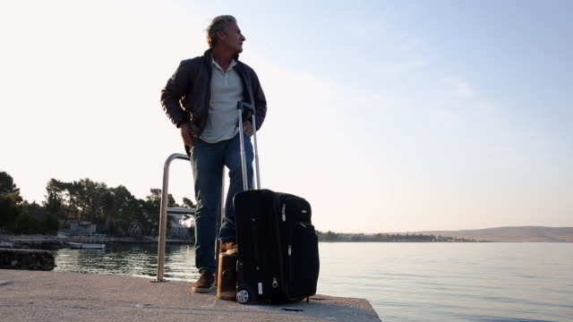 Man walks along sea promenade, with luggage