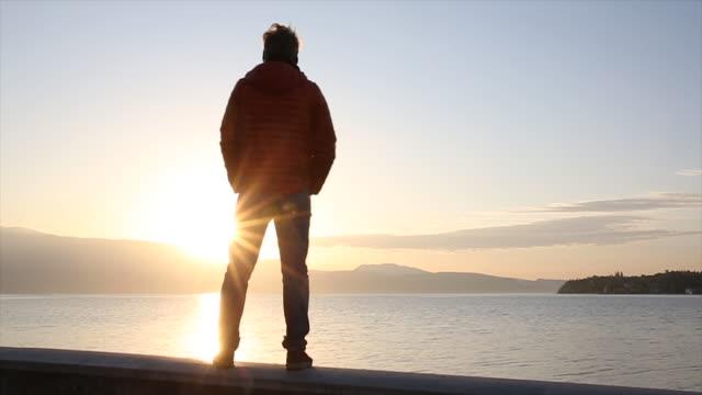 man walks along stone wall, looks across lake at sunrise - stone wall stock videos and b-roll footage