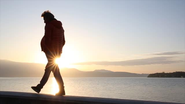 Man walks along stone wall, looks across lake at sunrise