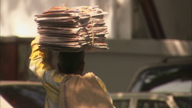 Man walks along street carrying newspapers for recycling on head Available in HD.