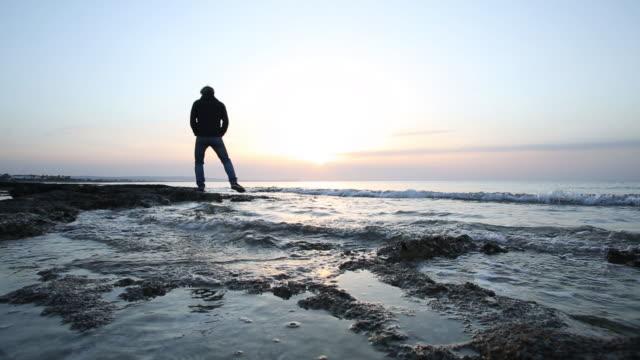 Man walks along tidal flat towards sunrise, at sea edge