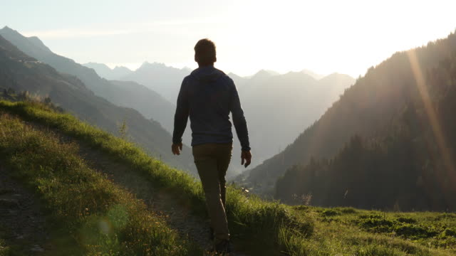 Man walks along track above mountain ranges, sunrise
