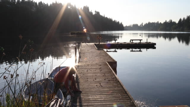 日出時,人類沿著木湖碼頭散步 - 僅一成熟男士 個影片檔及 b 捲影像