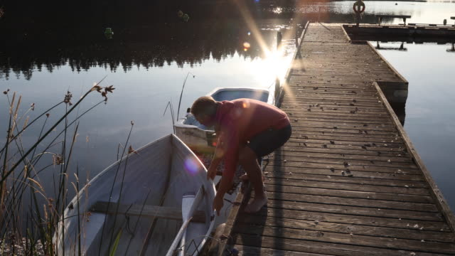 man walks along wooden lake dock at sunrise - untied stock videos and b-roll footage