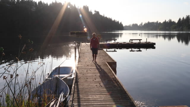 man walks along wooden lake dock at sunrise - only mature men stock videos & royalty-free footage