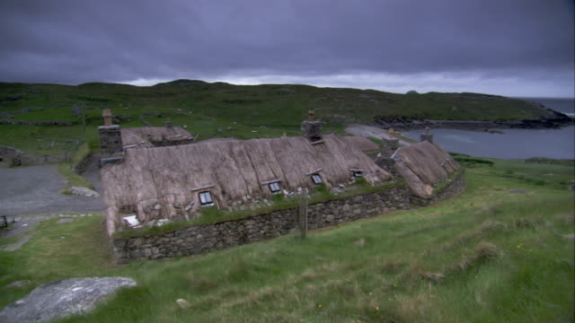 vídeos de stock e filmes b-roll de a man walks away from a blackhouse. available in hd. - telhado de palha