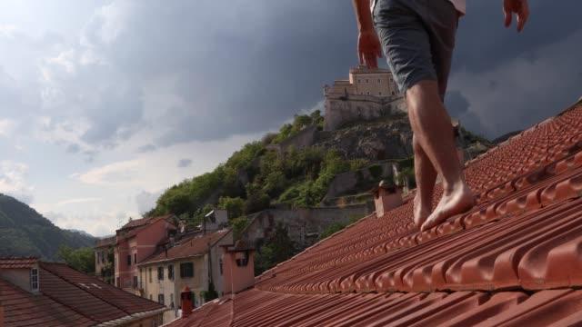 uomo cammina a piedi nudi sul tetto, scatta foto smartphone - top video stock e b–roll
