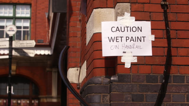 man walks behind a wet paint sign in windsor, england. - freshly painted stock videos & royalty-free footage