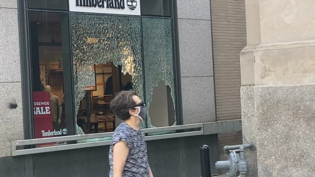 man walks by carrying plywood near a window shattered at a timberland store along michigan avenue after it was looted on august 10, 2020 in chicago,... - other stock videos & royalty-free footage