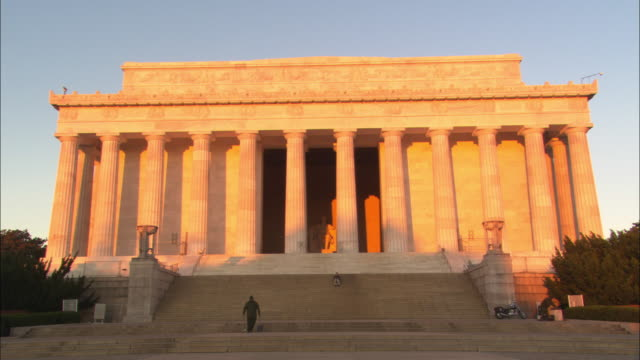 a man walks by the entrance of the lincoln memorial. - lincoln memorial stock videos & royalty-free footage