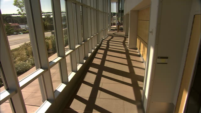 stockvideo's en b-roll-footage met a man walks down a bright hallway in a research facility. - universiteit van washington