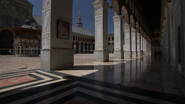 man walks down a covered passageway inside of the courtyard at the umayyad mosque in damascus, syria on august 18, 2018. - religion or spirituality stock videos & royalty-free footage