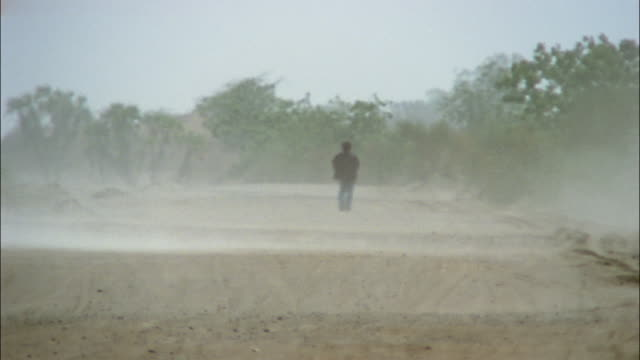 a man walks down a dirt road in a dust storm. - yemen stock videos and b-roll footage