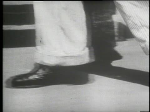 A man walks down a hallway through an open gate at Sing Sing prison in 1932