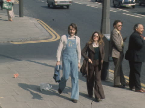 A man walks down a road wearing denim dungarees