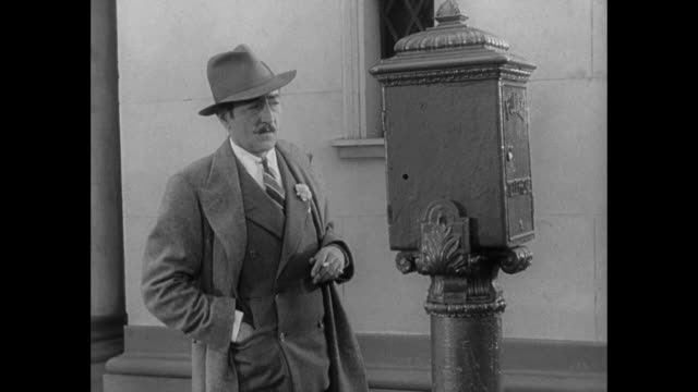1931 man (adolph menjou) walks down bustling city street and deliberately pulls fire alarm - 1931 stock videos & royalty-free footage
