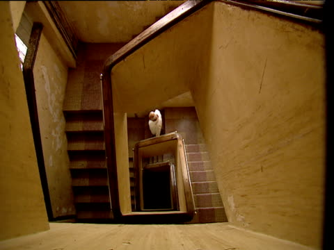 Man walks down spiral wooden stairs Bombay