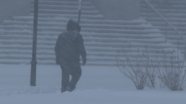 A man walks down the street in heavy snow during a powerful nor'easter in Waterbury Connecticut