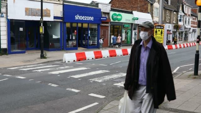 blackwood caerphilly wales september 08 a man walks down the street wearing a mask as a social distancing sign is displayed in the high street near a... - reaching stock videos & royalty-free footage