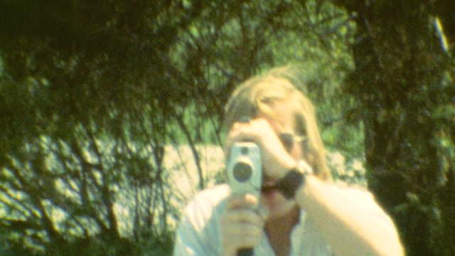 vídeos y material grabado en eventos de stock de a man walks forward while filming with a super 8 film camera / camera is shooting upside down as a teen walks forward / teens smiles / hidden camera... - 1970