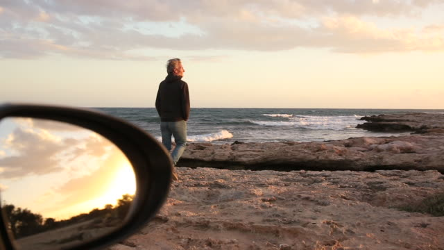 man walks from parked car, towards shoreline rocks and sea - republic of cyprus stock videos and b-roll footage