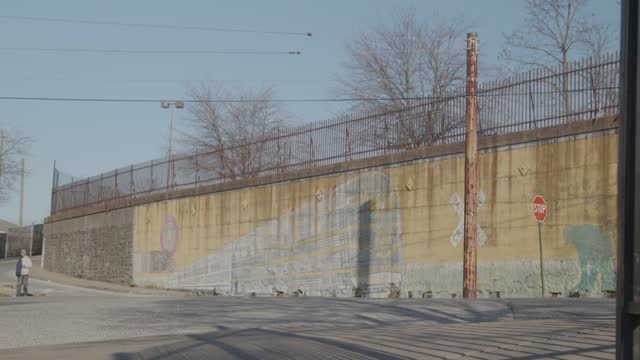 man walks in front of a mural of a train on february 26, 2021 in baltimore, maryland. the state's seven-day testing positivity rate was at 3.66% on... - mit handkamera stock-videos und b-roll-filmmaterial