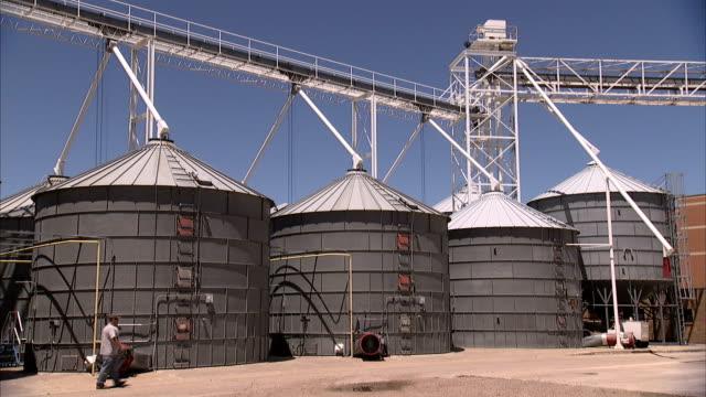 vidéos et rushes de a man walks in front of grain elevators. - silo