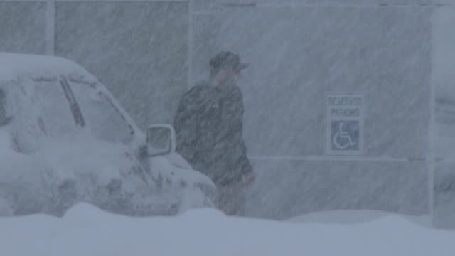 a man walks in near whiteout conditions in adams new york as very heavy snow falls during a lake effect snowstorm - scott mcpartland stock videos & royalty-free footage