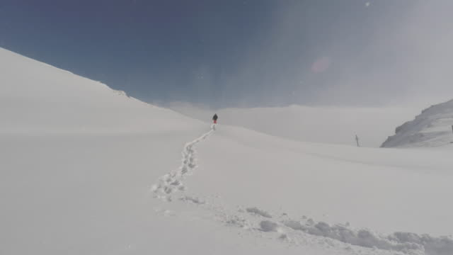 man walks in the snow in the mountains