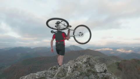vidéos et rushes de man walks in the top of a mountain with his bike over the shoulders. - seulement des jeunes hommes