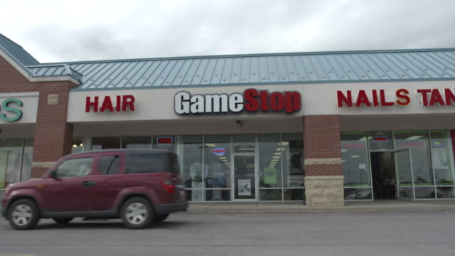 man walks into gamestop - centro commerciale suburbano video stock e b–roll