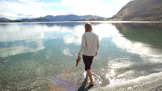 man walks into mountain lakeshore shallows at sunrise - lakeshore stock videos and b-roll footage
